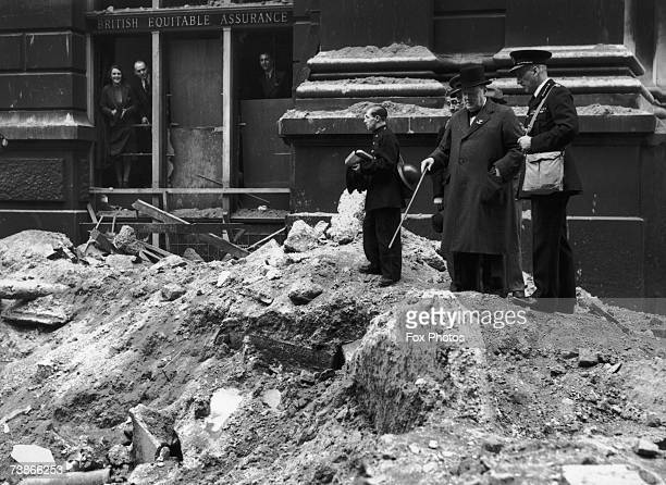 British prime minister Winston Churchill inspects bomb damage outside the London offices of the British Equitable Assurance after a World War II air...