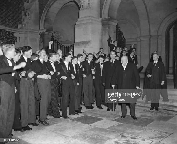 British Prime Minister Winston Churchill is cheered by the boys of Harrow School after a visit to his alma mater 7th November 1952