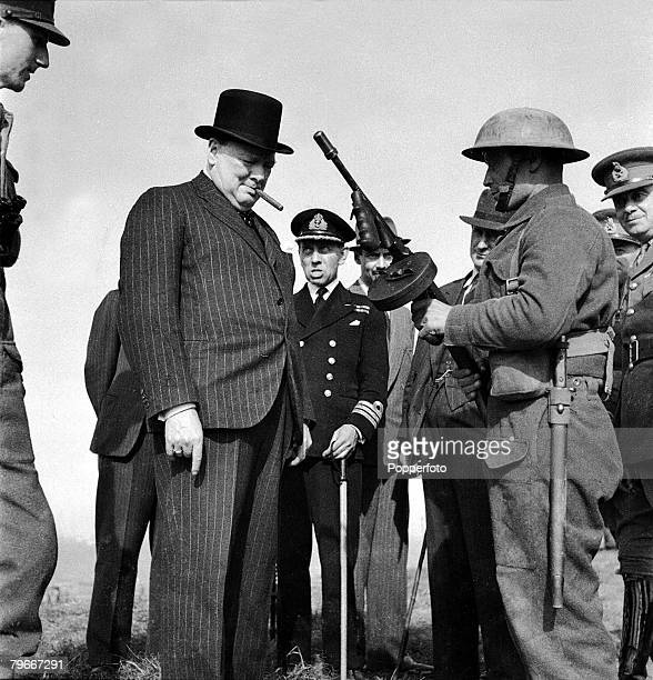 British Prime Minister Winston Churchill is shown an American Thompson submachine gun during an inspection of coastal fortifications and defences on...