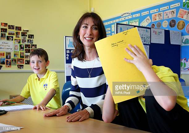British Prime Minister's wife Samantha Cameron talks to Joshua Westcott as he hides from the cameras as Joshua Jones looks on during a tour of Baston...
