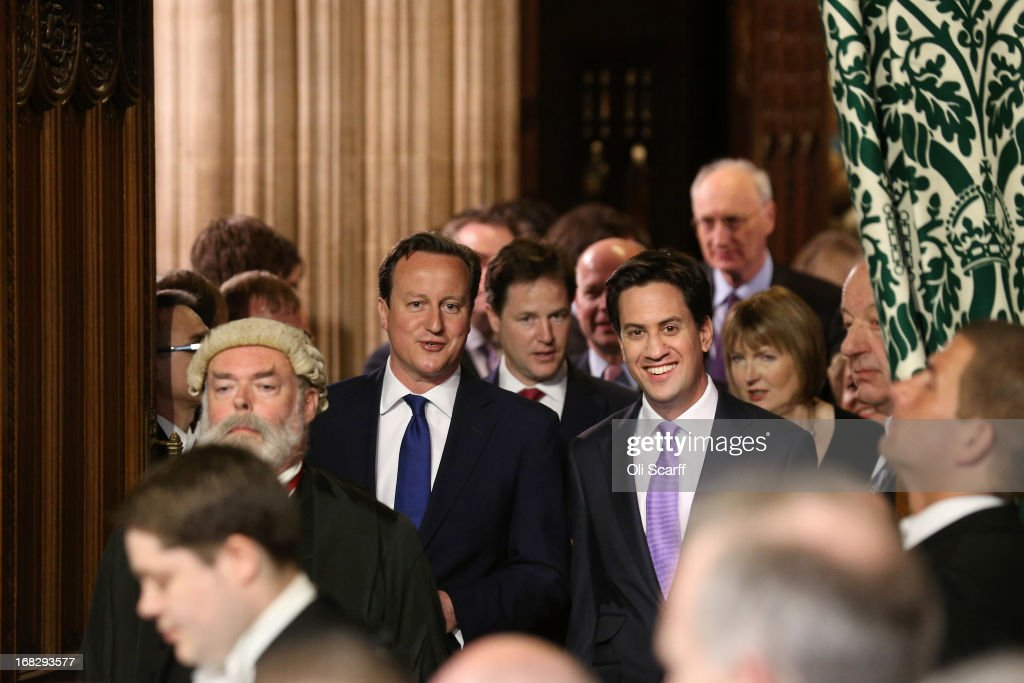 British Prime Minster David Cameron (3rd L) and Ed Miliband (4th R), the Leader of the Labour Party, walk through the Members' Lobby to listen to the Queen's Speech at the State Opening of Parliament on May 8, 2013 in London, England. Queen Elizabeth II unveiled the coalition government's legislative programme in a speech delivered to Members of Parliament and Peers in The House of Lords. Proposed legislation is expected to be introduced on toughening immigration regulations, capping social care costs in England and setting a single state pension rate of 144 GBP per week.