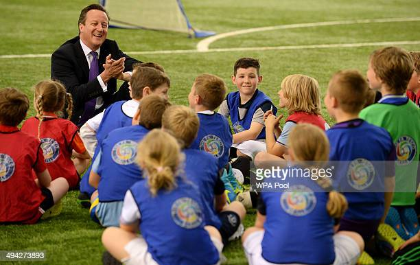 British Primeminister David Cameron meets school children during his visit to England's football training headquaters at St Georges Park on May 29...