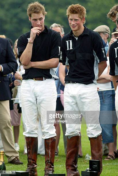 British Prince William and brother Prince Harry wait to recieve their prizes at the end of the Calcot Manor Hotel polo cup on June 22 2003 at Tetbury...