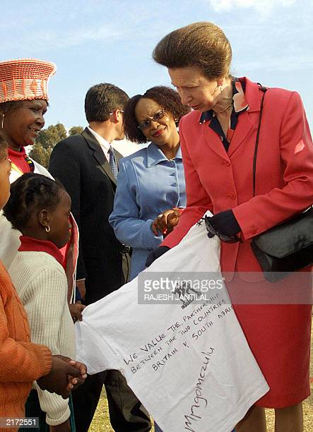 British Princess Royal Princess Anne receives a Tshirt from a youngster as a token of appreciation to her visit to Knack Soccer pitch in Alexander...