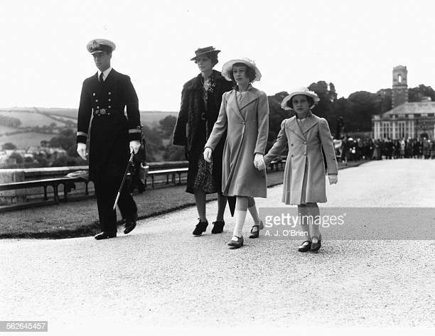 British princesses Elizabeth and Margaret holding hands accompanied by Lord and Lady Mountbatten walking through the grounds of the Royal Naval...