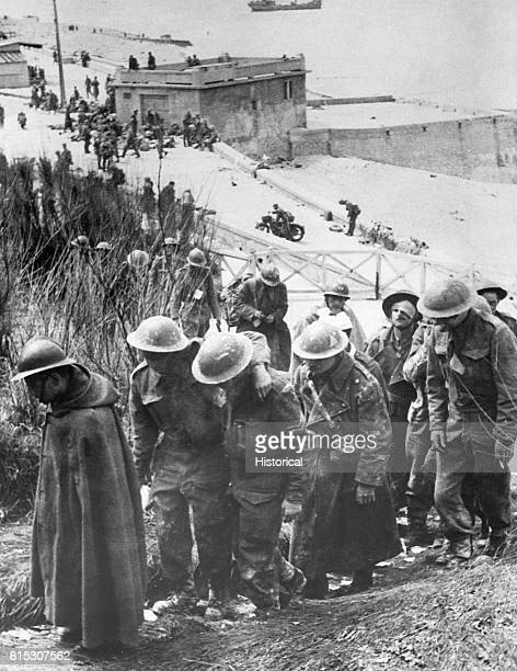 British prisoners of war captured at Dunkirk France in June 1940 walk dejectedly up a hill near a German fortification