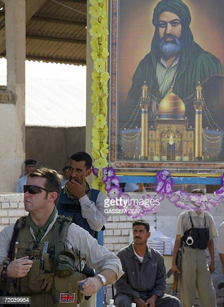British private security guard stands guard under the painting of Shiites most revered Imam Ali during a graduation ceremony of police recruits in...