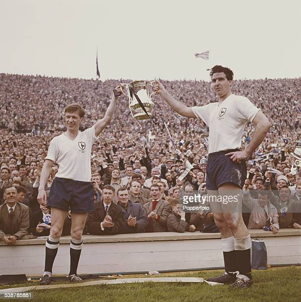 British professional footballers John White and Maurice Norman hold the Football Association Challenge Cup trophy aloft in front of crowds after...