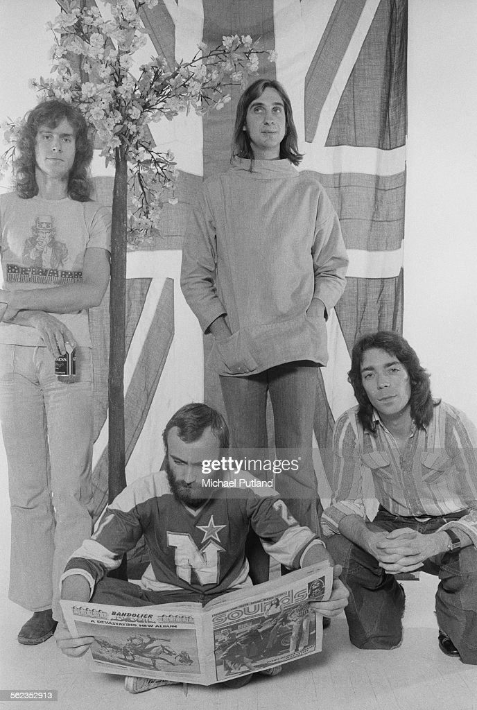 British progressive rock group Genesis posing in front of a union jack flag, 4th September 1975. Left to right: keyboard player Tony Banks, singer/drummer Phil Collins, bassist Mike Rutherford and guitarist Steve Hackett.