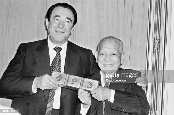 British publisher Robert Maxwell and Japanese businessman Ryoichi Sasakawa holding a metal ingot at a press conference in London 29th October 1980...