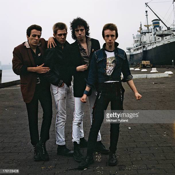 British punk group The Clash on a quayside in New York Harbor, 1978. Left to right: singer Joe Strummer , bassist Paul Simonon, guitarist Mick Jones...
