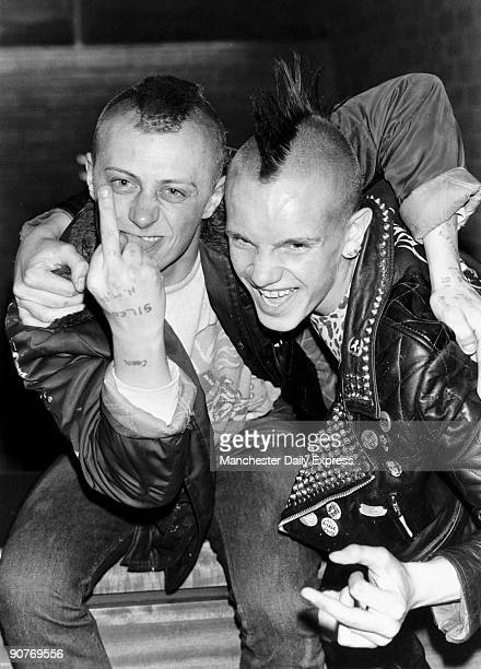 British punks with Mohican hairstyles and leather jackets The man on the left is �giving the finger� he appears to have a prison tattoo on his hand...