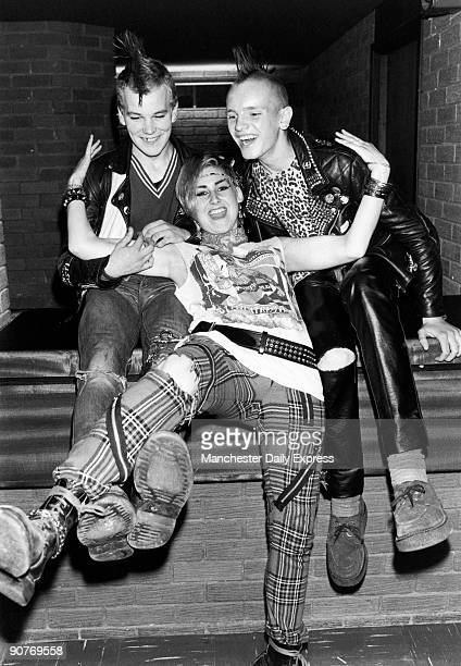 British punks with Mohican hairstyles wearing leather jackets tartan trousers with zips