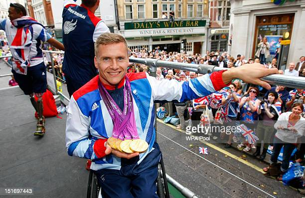 British quadruple gold medal winning Paralympian David Weir shows his four gold medals as he takes part in the London 2012 Victory Parade for Team GB...