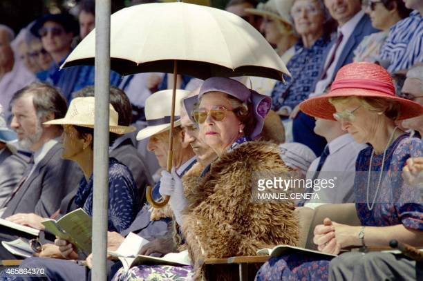 British Queen Elizabeth II shielding herself from the sun with an umbrella Prince Philip Duke of Edinburgh New Zealand Prime Minister Geoffrey Palmer...