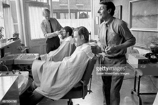 British racecar driver and team owner Graham Hill sits in a barber's chair, London, England, January 1970.