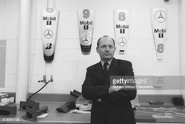 British racecar manager Ron Dennis stands in front of hoods at the McLaren Formula 1 workshops in Woking