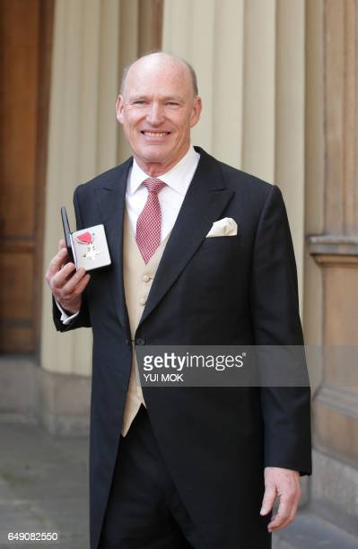 British racehorse trainer John Gosden poses with his medal after he was appointed a Officer of the Order of the British Empire for services to...