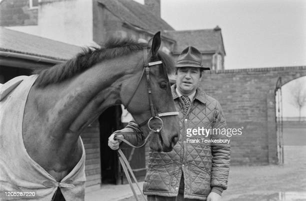 British racehorse trainer Michael Oliver holding the reins of one of his horses at his stables in Elmley Lovett, Worcestershire, England, 27th March...