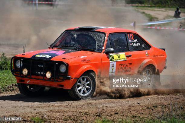 British racer John Lloyd with Kenya's Quentin Mitchel negotiate a turn in their classic Ford Escort at a spectator section on July 6 during the...