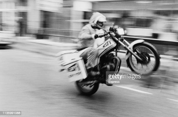 British racing driver Damon Hill doing a a wheelie while working as a motorcycle courier, UK, 15th December 1983.