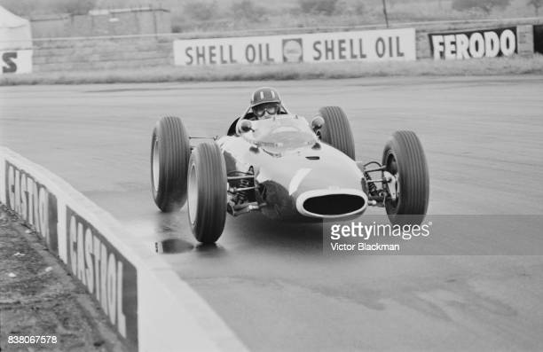British racing driver Graham Hill drives team British Racing Motors, BRM P57 V8, during the British Grand Prix at Silverstone, UK, 20th July 1963.