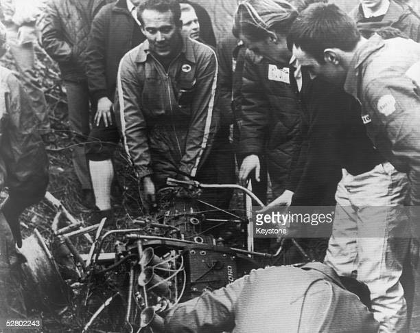 British racing driver Graham Hill is among those viewing the wreckage of the car driven by British racing driver Jim Clark at the time of his fatal...