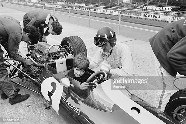 British racing driver Graham Hill overseeing his son Damon in the driving seat at the Silverstone Circuit, 27th April 1967.