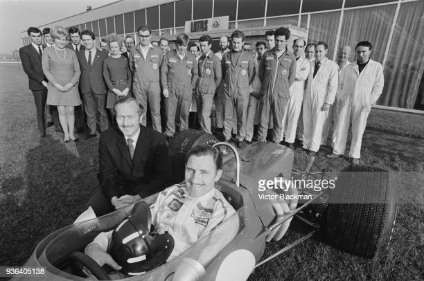 British racing driver Graham Hill , sitting inside the Lotus 49, founder of Lotus Cars Colin Chapman and his team of mechanics, designers and...