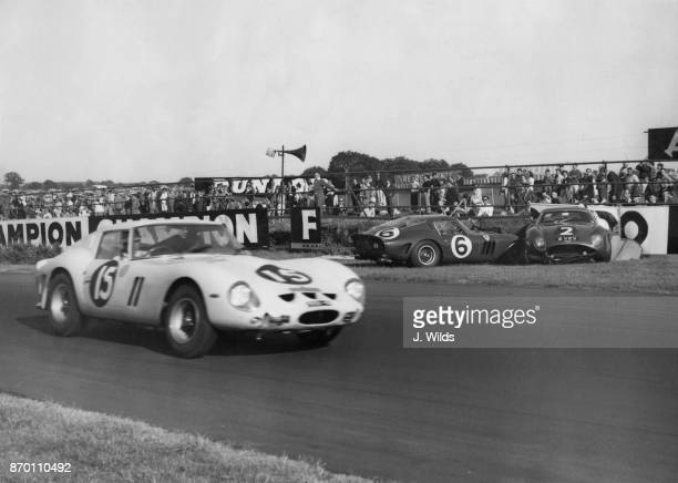 British racing driver Innes Ireland drives his 3 litre V12 Ferrari past the crash involving John Surtees' Ferrari and Jim Clark's Aston Martin to win...