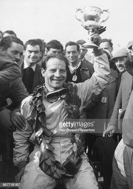 British racing driver Innes Ireland holding the Glover Trophy in the air after winning the race at Goodwood England April 18th 1960