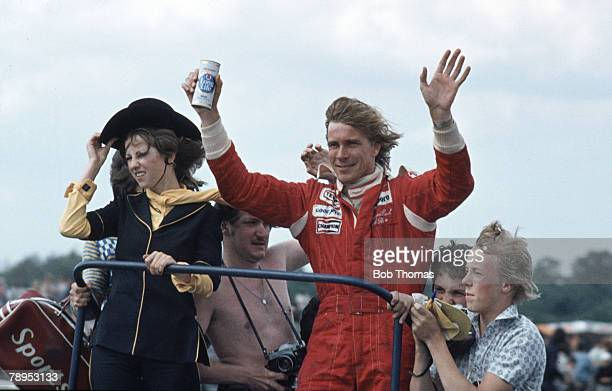 British racing driver James Hunt holds a can of Ind Coope Long Life beer as he waves to the crowd after driving the Marlboro Team McLaren McLaren M26...