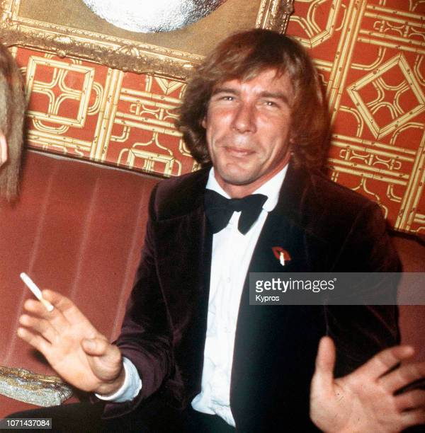 British racing driver James Hunt smoking a cigarette while attending a red carpet event, circa 1990.