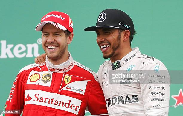 British racing driver Lewis Hamilton of team Mercedes AMG celebrates with Sebastian Vettel of team Ferrari after winning the Canadian Formula 1 Grand...