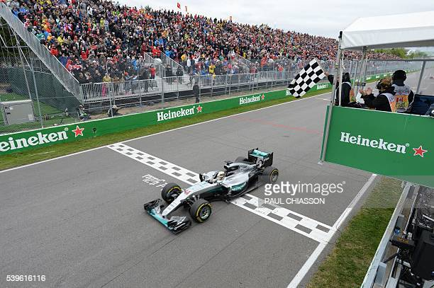 British racing driver Lewis Hamilton of team Mercedes receives the checkered flag to win the Canadian Grand Prix June 12 2016 in Montreal / AFP /...