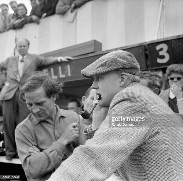 British racing driver Mike Hawthorn wearing a flat cap and smoking a pipe, in the pit during the Friday practice session of the British Grand Prix,...