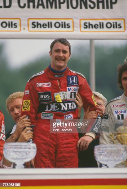British racing driver Nigel Mansell driver of the Canon Williams Honda Williams FW11 Honda RA166E 15 V6t pictured on the podium after finishing in...