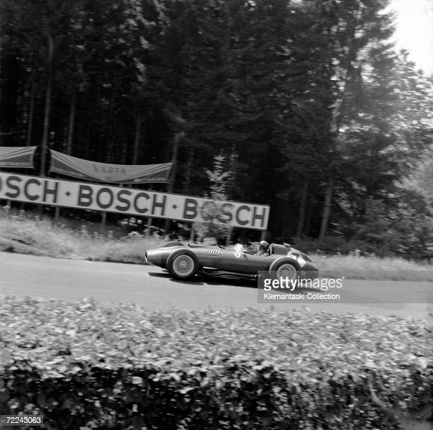 British racing driver Peter Collins at speed in his Ferrari Lancia 801 through one of the Nurburgring's many corners during the German Grand Prix,...