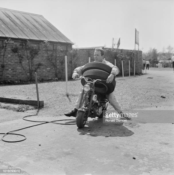 British racing driver Peter Gethin carrying two tires on a mini bike at Silverstone Circuit UK 14th May 1965