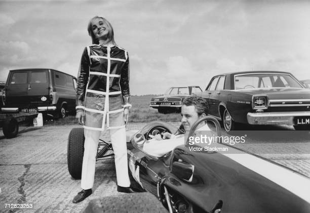 British racing driver Piers Courage sits aboard the Charles Lucas Team Lotus Lotus 41 Ford Cosworth as his wife Lady Sarah Curzon also known as Sally...