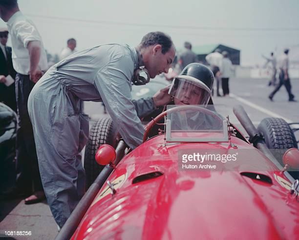 British racing driver Stirling Moss adjusts the helmet of Ferrari driver Mike Hawthorn before a race 1958