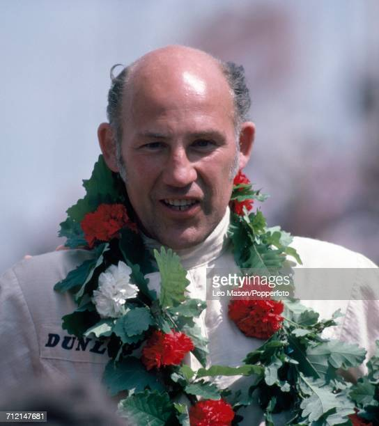 British racing driver Stirling Moss pictured wearing a garland of oak leaves and chrysanthemum flowers after finishing in first place in the Historic...