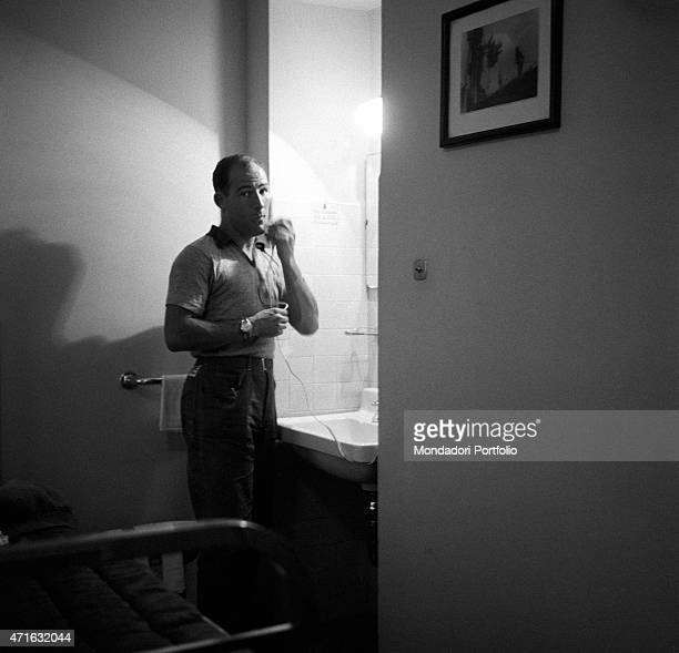 'British racing driver Stirling Moss shaving with an electric shaver at the Mille Miglia Automobile Race Italy April 1956 '