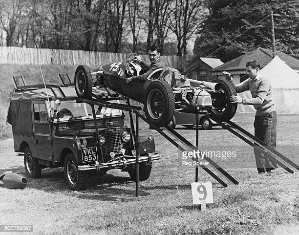 British racing driver Stuart Lewis-Evans at the wheel of his Cooper 500 Formula 3 car as it is loaded from a home-made ramp onto the roof of a Land...