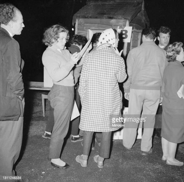 British racing drivers Pat Moss and Ann Wisdom check in looking tired after finishing the International RAC rally at Crystal Palace, 23rd November...