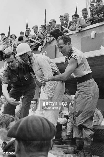 British racing drivers Peter Walker and Stirling Moss at 24 Hours of Le Mans in France, June 1953. On the left is Jaguar team manager Lofty England ....