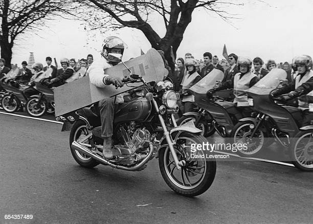 British racing motorcyclist Barry Sheene carrying a cutout of a pillar box in order to demonstrate what you should not carry on a motorcycle at a...