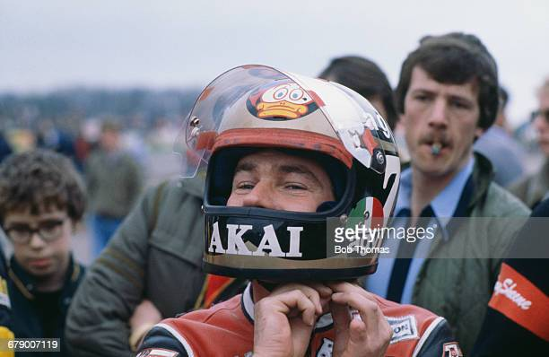 British racing motorcyclist Barry Sheene putting on his helmet at a race meeting circa 1980