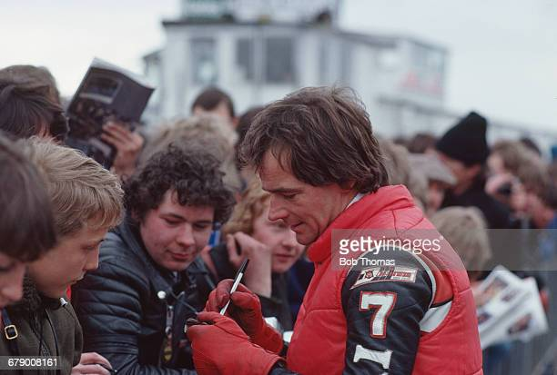 British racing motorcyclist Barry Sheene signs autographs for fans at a race meeting circa 1984