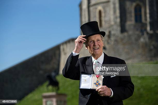 British radio and television presenter Nicholas Parsons poses with his Commander of the Order of the British Empire medal given to him by Queen...